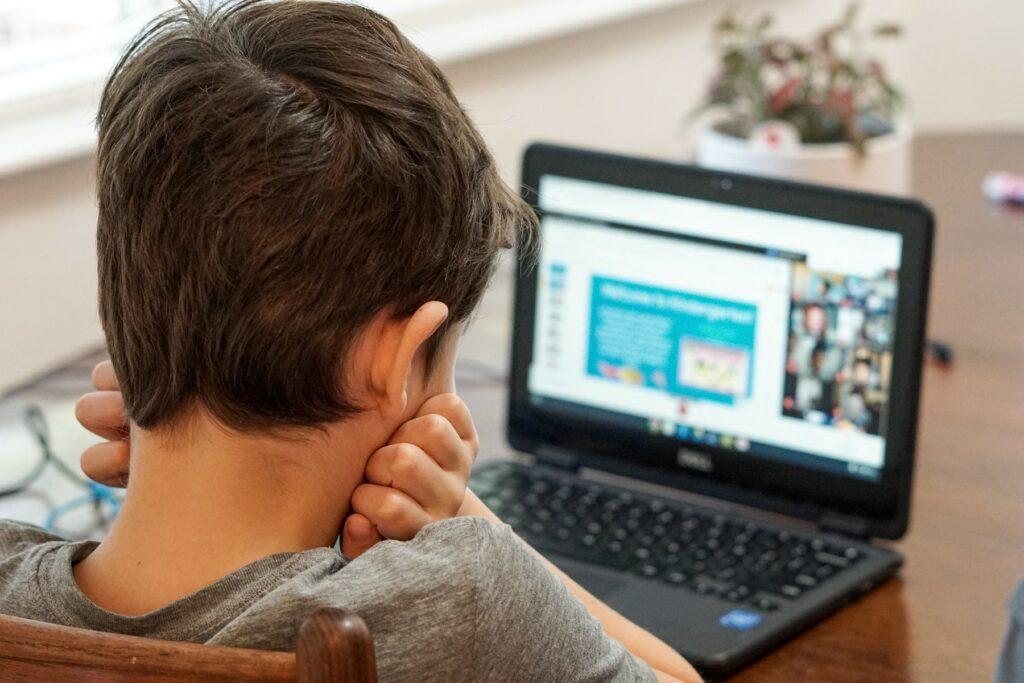 Fant sedi pri računalniku in si podpira glavo
