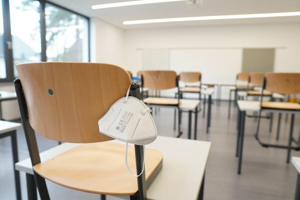 Prazna učilnica z zaščitno masko, obešeno na stol.